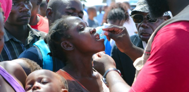 A woman receives an oral cholera vaccination at a camp for displaced survivors of cyclone Idai in Beira, Mozambique, Wednesday, April, 3, 2019. A cholera vaccination campaign is kicking off to reach nearly 900,000 cyclone survivors in Mozambique as officials rush to contain an outbreak of the disease.