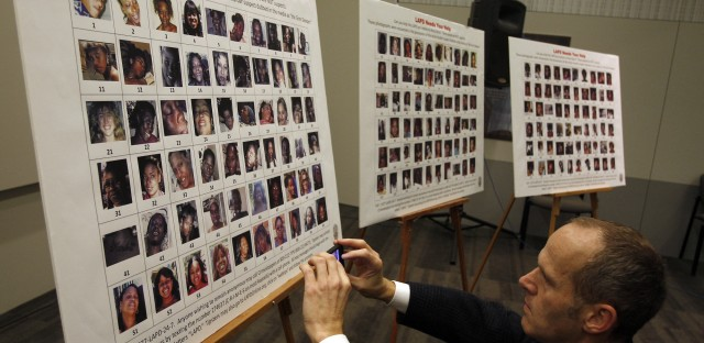 Frank Stoltze, a reporter for Southern California Public Radio, takes a photo of the 180 photographs and video stills of 160 women displayed at a press conference. The photos and stills were found in Lonnie Franklin Jr.'s possession.