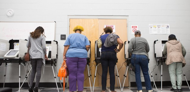 Voters cast ballots during early voting last week in Atlanta. Georgia has blocked approximately 53,000 voter registrations.