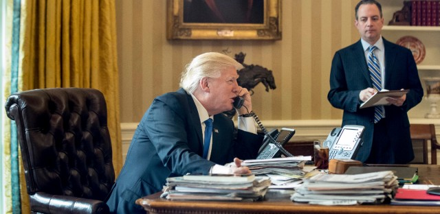President Donald Trump, accompanied by Chief of Staff Reince Priebus speaks on the phone with Russian President Vladimir Putin, Saturday, Jan. 28, 2017, in the Oval Office at the White House in Washington.