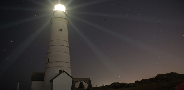 Boston Light, America's first lighthouse, beams light across the night sky.
