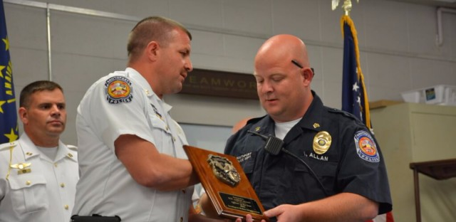 Southport Police Chief Thomas Vaughn presents a plaque in recognition of the 2015 Officer of the Year to Sgt. Aaron Allan.