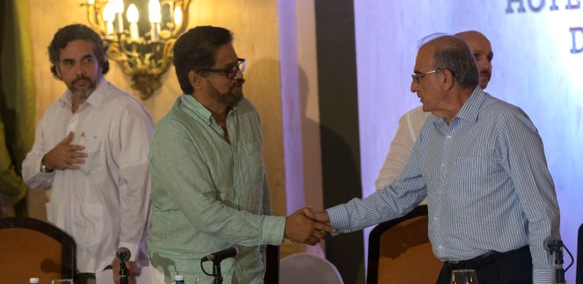 Humberto de la Calle, right, head of Colombia's government peace negotiation team, shakes hands with Ivan Marquez, chief negotiator of the Revolutionary Armed Forces of Colombia (FARC) in Havana, Cuba, Sunday, May 15, 2016. Colombia's government and the rebel Revolutionary Armed Forces of Colombia say they have agreed on the return of a handful of children living in the group's camps to civilian life.