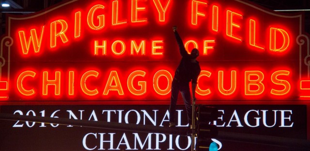 A Cubs fan celebrates on a traffic light at the intersection of Clark and Addison after the Cubs won the National League Championship.