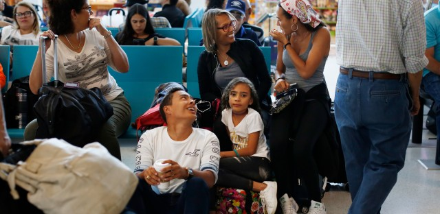 Glisela Vega Rivera and her three children wait to board a flight to Miami. The family is relocating to Doral, Fla., where her two older kids will start school at Ronald W. Reagan/Doral High School next week.