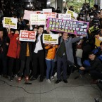 Anti-government protesters demonstrate as Choi Soon-sil, a confidante of South Korean President Park Geun-hye, appears at the Seoul Central Prosecutors' Office on Monday.