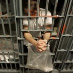 An inmate leans out the bars of his cell in a one–-prisoner-per-cell block in downtown Los Angeles.