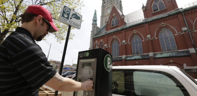Kyle Vocelka buys some time for his vehicle from a Chicago parking meter kiosk across the street from St. Alphonsus Catholic Church in this 2013 photo. (AP Photo/M. Spencer Green)