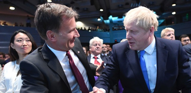 """Jeremy Hunt, left, congratulates Boris Johnson after the announcement of the result in the ballot for the new Conservative party leader, in London, Tuesday, July 23, 2019. Brexit hardliner Boris Johnson won the contest to lead Britain's governing Conservative Party on Tuesday and will become the country's next prime minister, tasked with fulfilling his promise to lead the U.K. out of the European Union """"come what may."""""""