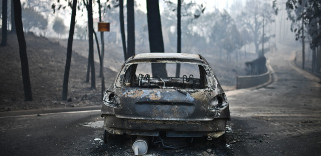 A burnt car rests on a road shortly after a wildfire swept through central Portugal. Most of the dozens of victims were caught in their cars in the area after the blaze broke out Saturday afternoon local time.