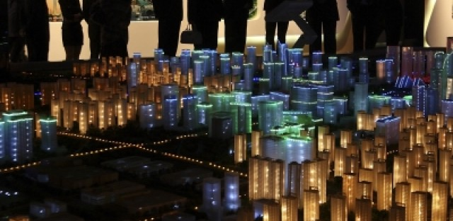 Visitors look at a model for real estate development in Chengdu, China.