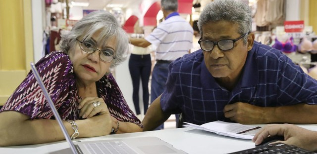 Isabel Diaz Tinoco and Jose Luis Tinoco had some questions for the Miami insurance agent who helped guide them in signing up for a HealthCare.gov policy at the Mall of the Americas in November. Joe Raedle/Getty Images