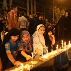 People light candles at the scene of a massive car bomb attack in Karada, a busy shopping district where people were shopping for the upcoming Eid al-Fitr holiday, in the center of Baghdad, Iraq, Monday, July 4, 2016.