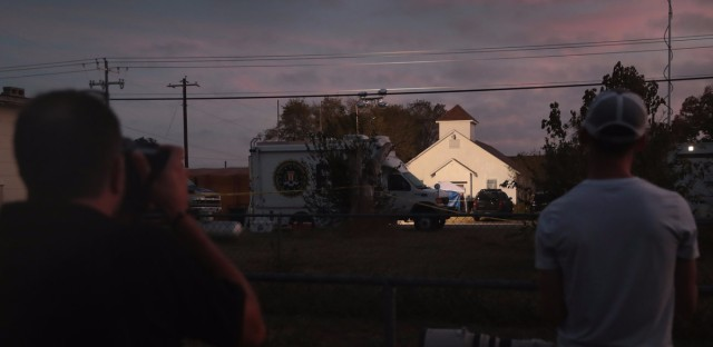 Newspaper photographers look on as the sun rises over the First Baptist Church in Sutherland Springs, Texas, on Monday. The day before, a gunman identified as Devin Patrick Kelly killed 26 people and wounded many more when he opened fire during a Sunday service. (Scott Olson/Getty Images)