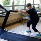In this Aug. 15, 2017, photo, Rita Driscoll stretches before she walks on a treadmill at University of Minnesota Medical Center in Minneapolis. After years of leg pain slowing her down, Driscoll learned she has peripheral artery disease, or PAD. Medicare soon will start paying hospitals and clinics for these exercise sessions, making the therapy available for thousands of older Americans with a specific type of leg pain. (AP Photo/Jim Mone)