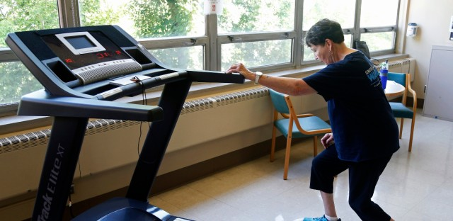 In this Aug. 15, 2017, photo, Rita Driscoll stretches before she walks on a treadmill at University of Minnesota Medical Center in Minneapolis. After years of leg pain slowing her down, Driscoll learned she has peripheral artery disease, or PAD. Medicare soon will start paying hospitals and clinics for these exercise sessions, making the therapy available for thousands of older Americans with a specific type of leg pain.