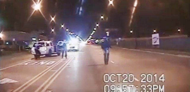 Laquan McDonald (right) walks down the street moments before being shot by Officer Jason Van Dyke in Chicago in October 2014, in a still shot from a police dashcam video.