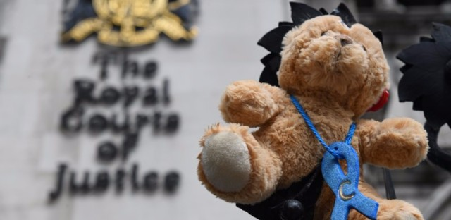 A picture shows a teddy bear set up by supporters of the family of British baby Charlie Gard outside the Royal Courts of Justice in London on Monday. After months of legal conflict over whether an experimental treatment might help Charlie or would only cause suffering, the baby will be transferred to a hospice facility to die.