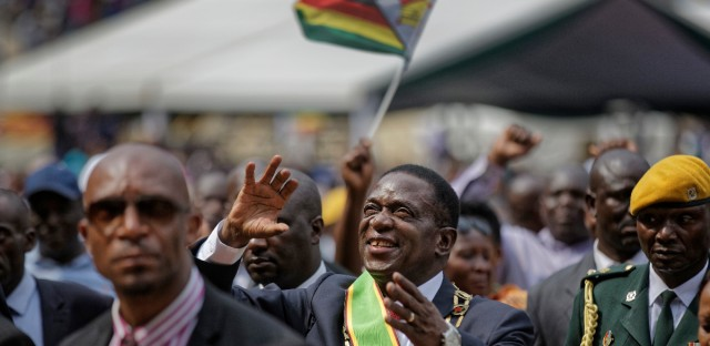 Zimbabwe's President Emmerson Mnangagwa, center, gestures to the cheering crowd as he leaves after the presidential inauguration ceremony in the capital Harare, Zimbabwe Friday, Nov. 24, 2017. Mnangagwa was sworn in as Zimbabwe's president after Robert Mugabe resigned on Tuesday, ending his 37-year rule.