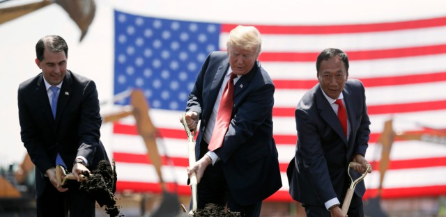In this June 28, 2018, file photo, President Donald Trump, center, along with Wisconsin Gov. Scott Walker, left, and Foxconn Chairman Terry Gou participate in a groundbreaking event for the new Foxconn facility in Mt. Pleasant, Wis. To make the next generation of liquid crystal display technology, Foxconn Technology Group will draw talent from beyond the borders of Wisconsin, partner with universities and technical schools and even tap into transitioning members of the military to find the 13,000 workers it eventually expects to hire.