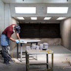 A man sands a table in an industrial spray room