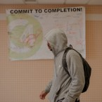 Luis walks through the hallways of Wrigh College in a gray hoodie. A sign behind him reads 'Commit to Completion'