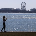 FILE - In this March 24, 2017 file photo, a lone woman walks the trail along Lake Michigan at Chicago' North Avenue beach. President Donald Trump's administration says it's time for state and local governments to pay for cleanups of iconic but polluted waterways such as the Great Lakes, Chesapeake Bay and Puget Sound. The proposed federal budget for 2018 would eliminate $427 million for regional water restoration initiatives.