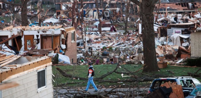 A man walks through what is left of a neighborhood in Washington, Ill., on Monday, Nov. 18, 2013, a day after a tornado ripped through the central Illinois town. The tornado cut a path about an eighth of a mile wide from one side of Washington to the other and damaged or destroyed as many as 500 homes.
