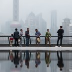 "People in Shanghai overlook the financial district in June 2016. The Shanghai city government recently released an app that produces a ""public credit score"" for residents. A good score can lead to discounts, but a bad score can cause problems."