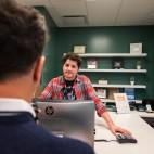 A man stands behind a counter at MedMar dispensary looking at a customer