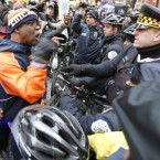 In this Dec. 24, 2015 file photo, protesters yell at Chicago Police officers at a bicycle barricade in Chicago. A day after a task force blasted the Chicago Police Department for decades of discrimination Wednesday, April 13, 2016, city and law enforcement officials weighed which of the panel's recommendations could be adopted and how much they might cost.