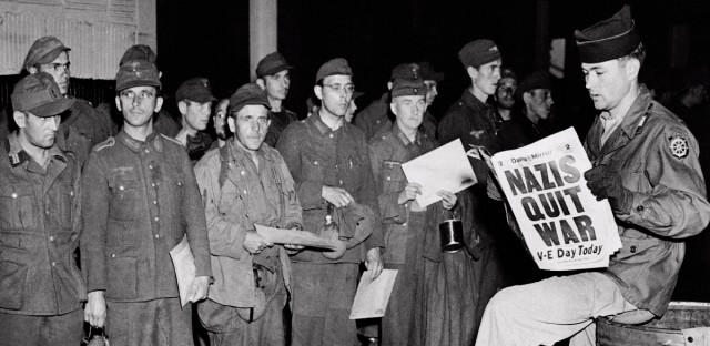 Pfc. Clarence K. Ayers of Evansville, Ind., reads the news of V-E Day as newly arrived German prisoners stand of a New York City pier, May 8, 1945. (AP Photo/John Rooney)