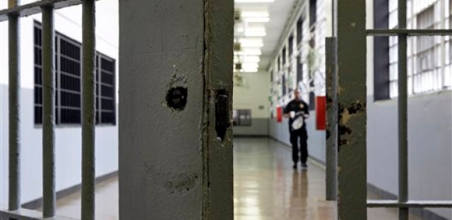 An open gate awaits a guard as he walks down a hall in the now-closed men's section of the Baltimore City Detention Center, Thursday, Aug. 27, 2015, in Baltimore.