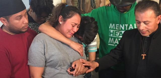 Adilene Marquina, middle, sobs after she announced she will be seeking sanctuary inside a church on Chicago's Southwest Side. Her son, Johan, hugs her, and Rev. Jose Landaverde comforts her.