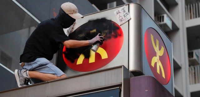 A protester sprays black paint on an MTR train logo to protest those injured on Aug 31 outside Prince Edward station in Hong Kong on Friday, Sept. 6, 2019. The ratings agency Fitch on Friday cut Hong Kong's credit rating and warned that conflict with anti-government protesters was hurting the image of its business climate.
