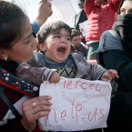 "In this March 3, 2016 file photo a child screams while holding paper that reads: ""Merkel Help Us"" as migrants block a railway during a protest demanding the opening of the border between Greece and Macedonia in the northern Greek border station of Idomeni."
