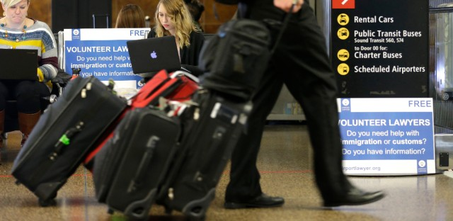 Asti Gallina, center, a volunteer law student from the University of Washington, working at a station near where passengers arrive on international flights at Seattle-Tacoma International Airport on Feb. 28, 2017. President Trump issued a revised executive order affecting immigration on Monday, March 6, 2017. (AP Photo/Ted S. Warren)