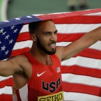 United States' Boris Berian holds the U.S. flag after he won the men's 800-meter sprint final during the World Indoor Athletics Championships, in Portland, Ore.