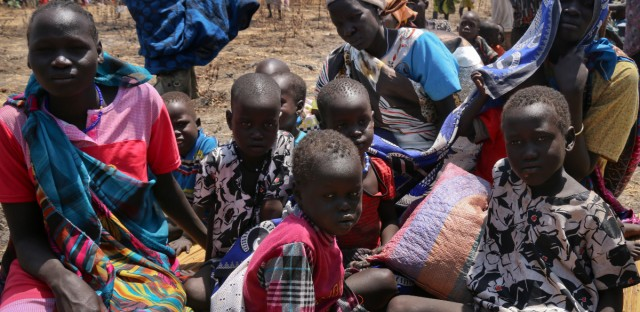 In this photo released by the World Food Programme (WFP), a family waits for food assistance to be distributed in Thonyor, Leer County, one of the areas in which famine has been declared, in South Sudan.