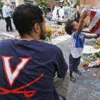 Pastor Daniel Xisto and his son Max, 2, look over a makeshift memorial on Monday for Heather Heyer, who was killed in a car attack on Saturday after a white nationalist rally in Charlottesville, Va. While many are calling the attack an act of domestic terrorism, U.S. federal law has no such specific criminal charge.