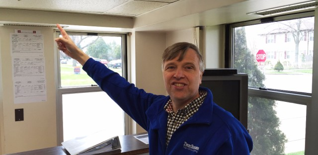 Twin Supplies owner Chris Skokna points at one of his light fixtures.