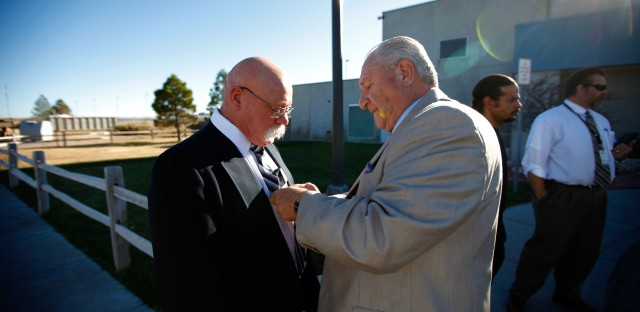 John Huckleberry (right) helps Ronald Boley tie his tie outside the Sterling Correctional Facility in Colorado. About once a month, the men — along with a group of other former inmates living in the Denver area — drive the two hours to Sterling to meet with members of the Long Term Offender Program, who are still behind bars but hoping to make their way out.