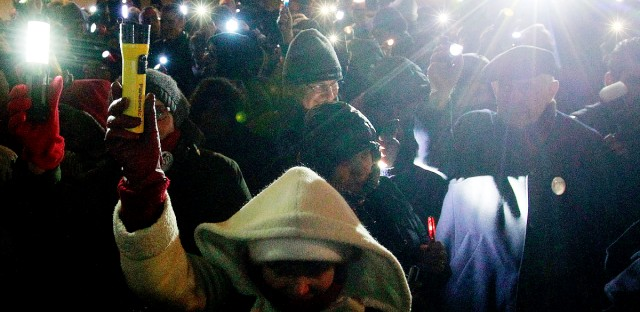 People use flashlight and mobiles to protest against new legislation to increase the government's surveillance powers in front of the Presidential Palace in Warsaw, Poland, Friday, Feb. 5, 2016. Poland's president approved new legislation to increase the government's surveillance powers, his office said on Thursday, despite fears that the new law undermines privacy.
