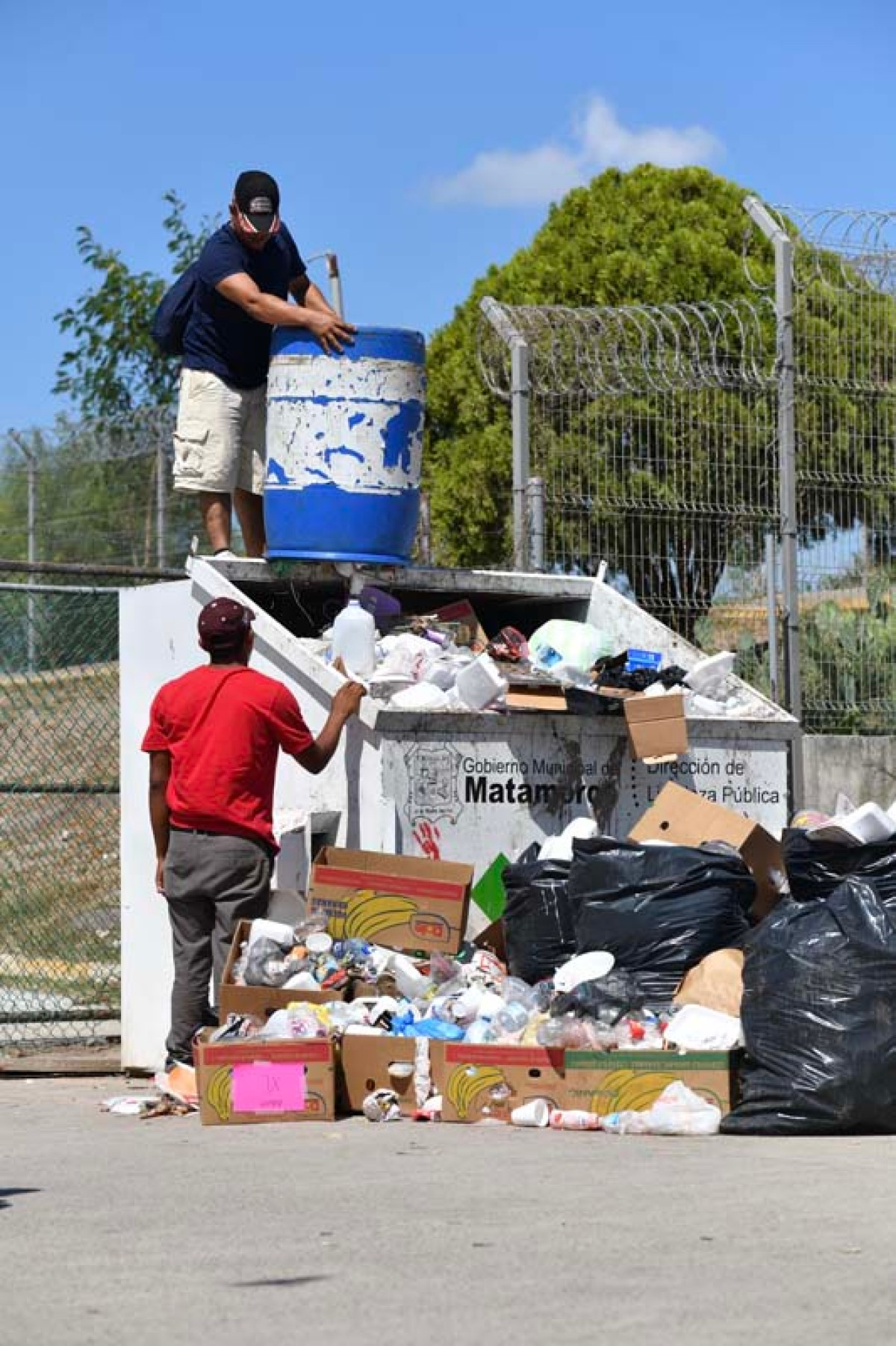 People move trash in Matamoros, Mexico
