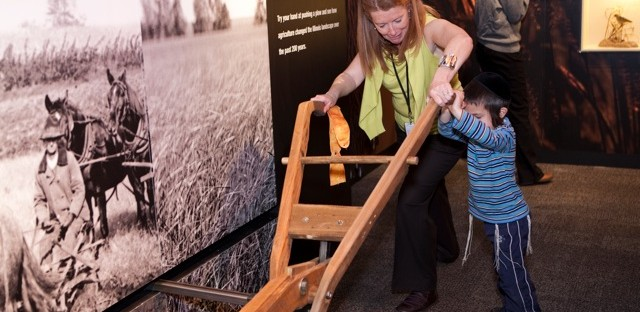 The Peggy Notebaert Nature Museum's President and CEO Deborah Lahey pushes a 19th-century plow replica with an exhibit guest.