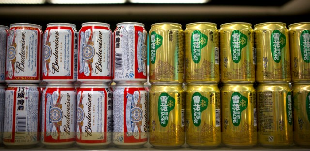 In this Thursday, Oct. 15, 2015 photo, cans of Budweiser beer, owned by AB InBev, sit next to cans of Snow beer, in which SABMiller has a 49 percent ownership stake, on a grocery store shelf in Beijing. A potential prize for AB InBev in its bid for SABMiller is a Chinese beer, Snow, that is the world's biggest seller. But any deal will face Chinese regulators who have barred the two brewing giants in the past from cooperating.