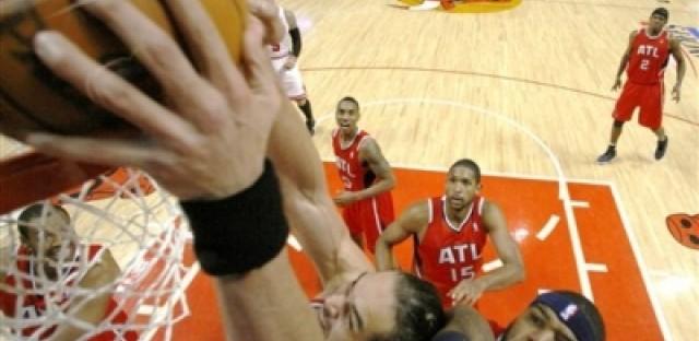 Chicago Bulls center Joakim Noah dunks past Atlanta Hawks forward Josh Smith during Game 5 of the 2011 NBA playoffs.