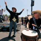 "Grateful Dead drummer Mickey Hart, left, Remo Belli, founder and CEO of Remo, Inc., center, and John Densmore, the drummer of the rock band The Doors, celebrate to the beat of ""Rock the Rhythm, Beat the Odds,"" a giant drum circle event at the College of the Canyons Cougar Stadium in Santa Clarita, Calif."