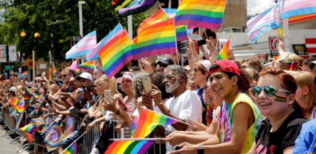 A crowd holds rainbow flags as they watch the 48th Annual Chicago Pride Parade on June 25, 2017.