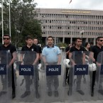 Turkish riot police stand guard outside a courthouse where prosecutors are questioning hundreds of coup plotters